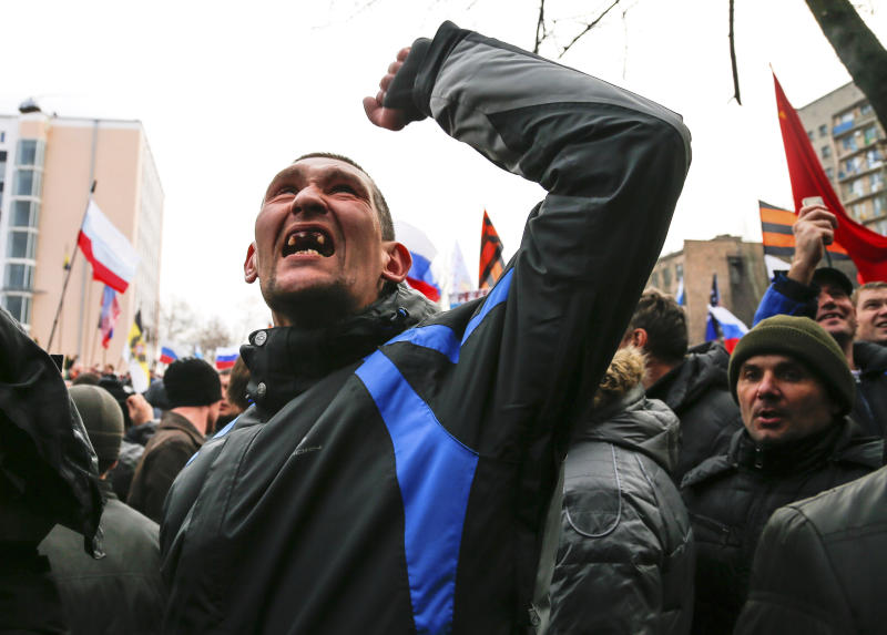 A pro-Russia demonstrator gestures as others storm the prosecutor-general's office during a rally in Donetsk, Ukraine, Sunday, March 16, 2014. Pro-Russia demonstrators in the eastern city of Donetsk called Sunday for a referendum similar to the one in Crimea as some of them stormed the prosecutor-general's office. (AP Photo/Andrey Basevich)