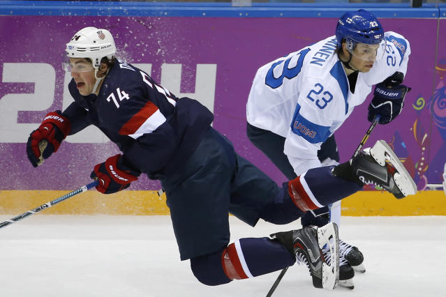 T. J. Oshie of the United States falls to the ice after battling Sakari Salminen of Finland during the first period of the men's bronze medal ice hockey game at the 2014 Winter Olympics, Saturday, Feb. 22, 2014, in Sochi, Russia. (AP Photo/Matt Slocum)