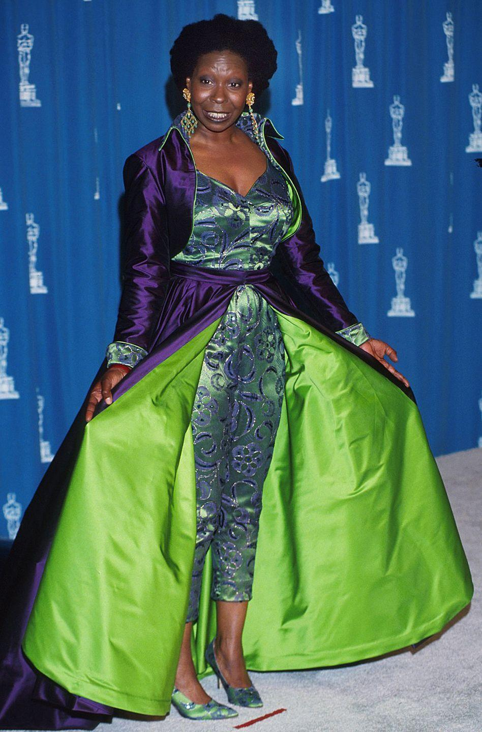 """<p>Whoopi was way ahead of the <a href=""""https://www.cosmopolitan.com/style-beauty/fashion/a23323743/neon-green-trend-2018/"""" rel=""""nofollow noopener"""" target=""""_blank"""" data-ylk=""""slk:neon-green trend"""" class=""""link rapid-noclick-resp"""">neon-green trend</a> that's been in full force lately, but at the Oscars, she paired the hue with deep purple and teal to make a can't-miss-it red-carpet ensemble. Like, wow, this is a LOT of color. </p>"""