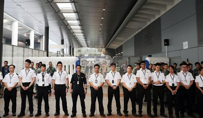 Airport security personnel form a line in front of the terminal. Photo: Sam Tsang