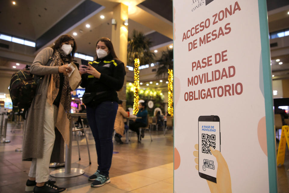 A worker checks a woman's QR code indicating she has two doses of vaccine against COVID-19 to allow her in the table area of a food court at a mall in Santiago on July 19, 2021, amid the COVID-19 pandemic. - Chile started Monday the relaxation of sanitary restrictions by reopening inside areas of bars and restaurants, and cinemas, after registering the lowers contagion rates since November. (Photo by JAVIER TORRES / AFP) (Photo by JAVIER TORRES/AFP via Getty Images)