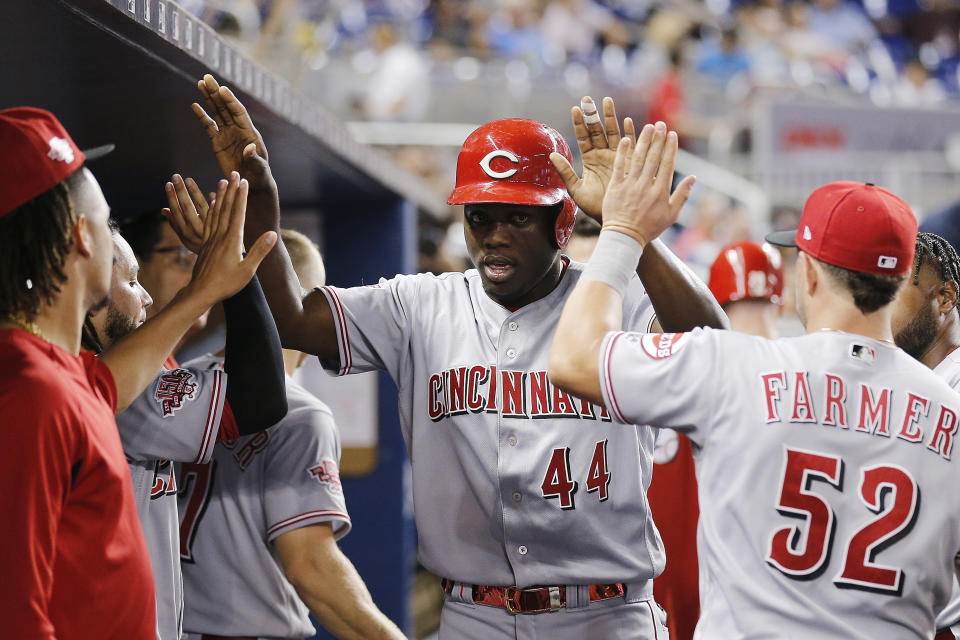 MIAMI, FLORIDA - AUGUST 28:  Aristides Aquino #44 of the Cincinnati Reds celebrates with teammates after scoring a run in the fourth inning against the Miami Marlins at Marlins Park on August 28, 2019 in Miami, Florida. (Photo by Michael Reaves/Getty Images)