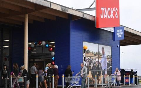 Customers pushing trollies coming in and out of Tesco's new Jack's store in Chatteris, Cambridgeshire, that has a red sign with white writing and and a decorative archway made out of blue, white and red balloons. - Credit: Jo Giddens/PA