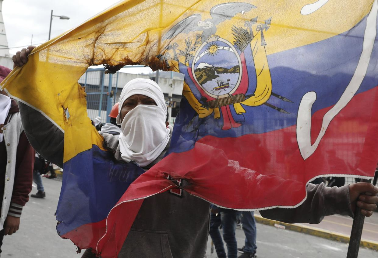 An anti-government demonstrator holds a damaged national flag during a protest march against President Lenin Moreno and his economic policies, in Quito, Ecuador, Oct. 8, 2019. (Photo: Fernando Vergara/AP)