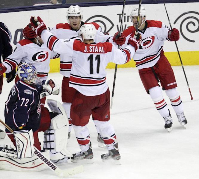 Carolina Hurricanes' Nathan Gerbe, from top left to right, Brett Bellemore, Jordan Staal, and Patrick Dwyer celebrate their game-winning goal in front of Columbus Blue Jackets' Sergei Bobrovsky (72)nam ice, of Russia, during the third period of an NHL hockey game on Thursday, Sept. 26, 2013, in Columbus, Ohio. The Hurricanes defeated the Blue Jackets 2-1. (AP Photo/Jay LaPrete)