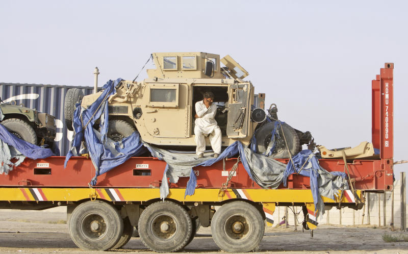 In this Friday, July 6, 2012 photo, Pakistani driver, Ihsanullah, 45, speaks on his mobile phone on top of a truck carrying NATO Humvees at a terminal in the Pakistani-Afghan border, in Chaman, Pakistan. As the United States trumpets its success in persuading Pakistan to end its seven-month blockade of supplies for NATO troops in Afghanistan, another group privately cheers its good fortune: the Taliban. One of the Afghan war's great ironies is that both NATO and the Taliban rely on the convoys to fuel their operations a recipe for seemingly endless conflict. (AP Photo/Matiullah Achakzai)