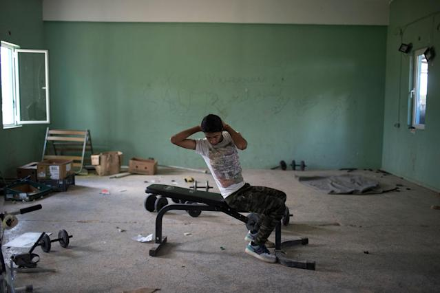<p>16-year-old Amor Biro from Syria works out at the refugee camp of Ritsona about 86 kilometers (53 miles) north of Athens, May 26, 2017. Amor and his family wants to go to Germany. On World Refugee Day, more than 60,000 refugees and migrants are still stranded in Greece in a process barely moving: Forward to other countries of the European Union, or back to Turkey under a deportation deal launched 15 months ago. (Photo: Petros Giannakouris/AP) </p>