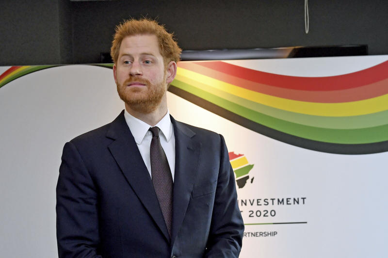 Prince Harry pictured in front of a colourful corporate sign