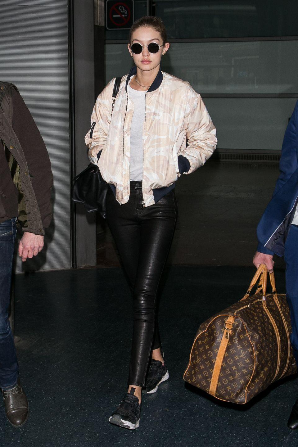 """<p>In tight leather leggings and a <a href=""""http://www.ganni.com/home"""" rel=""""nofollow noopener"""" target=""""_blank"""" data-ylk=""""slk:Ganni"""" class=""""link rapid-noclick-resp"""">Ganni</a> pastel bomber jacket at Aeroport Roissy in Paris, France.</p>"""