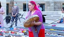 Chantal Chagnon drums at a vigil in Calgary for the children of Kamloops Indian Residential School on Tk'emlups te Secwépemc First Nation. Shoes, representing the 215 childrens' bodies found buried at the former school site in B.C. this week, were laid on the steps of city hall.