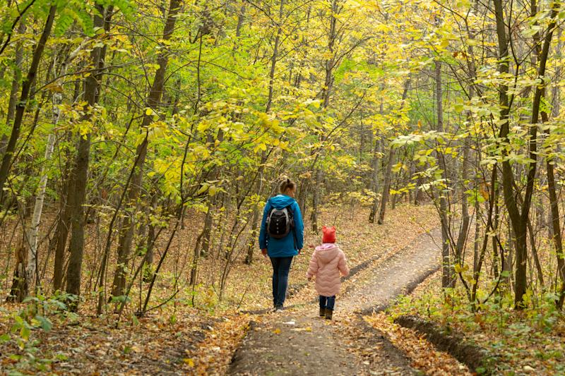 Mother and daughter are walking in the autumn forest
