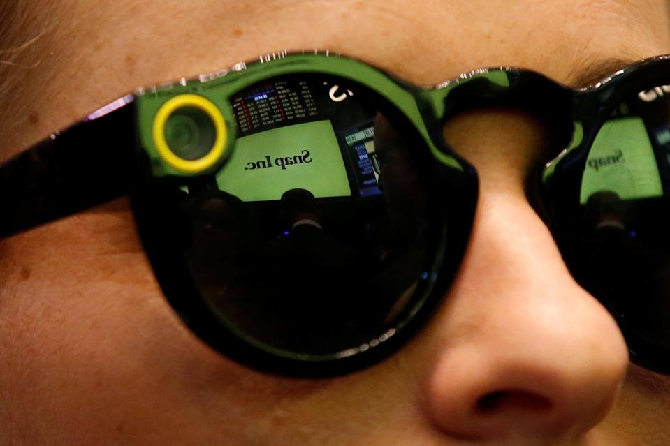 A woman wearing Snapchat Spectacles waits for Snap Inc. to list their IPO on the NYSE, March 2, 2017. REUTERS/Brendan McDermid