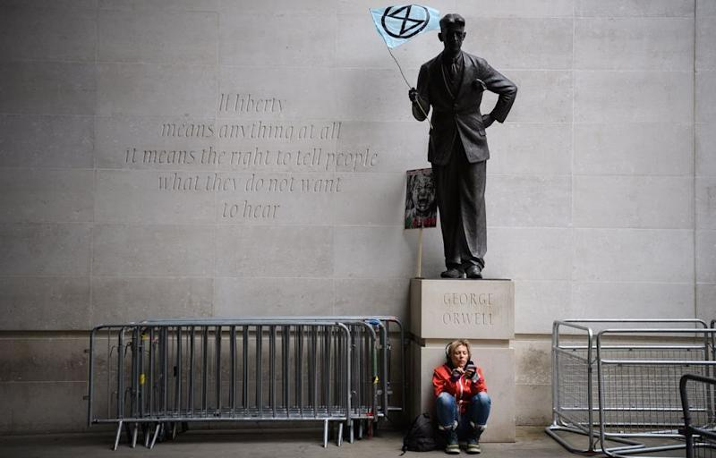 LONDON, ENGLAND - OCTOBER 11: An Extinction Rebellion flag is seen in the hands of a statue of author George Orwell outside the headquarters of the BBC as the environmental group protests about the broadcaster's alleged silence over climate issues on October 11, 2019 in London, England. The Extinction Rebellion group is in the middle of a string of protests across the country, with the aim of highlighting the urgency to address climate change as an ongoing emergency. (Photo by Leon Neal/Getty Images)