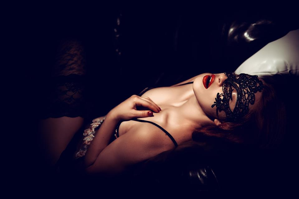 sexy woman wearing lace lingerie and black mask on her eyes.