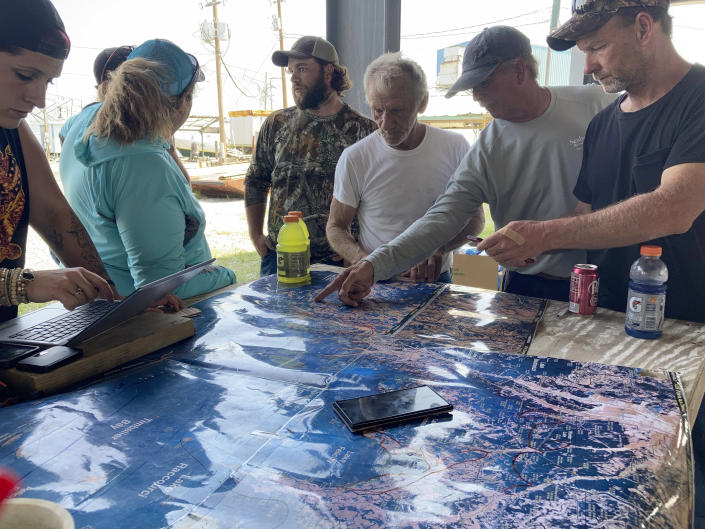 Volunteers gather around a map of the Louisiana coast on Thursday, April 30, 2021, in Cocodrie, La., as they search for survivors of the Seacor Power, a lift boat that capsized off the coast on April 13. (AP Photo/Rebecca Santana)