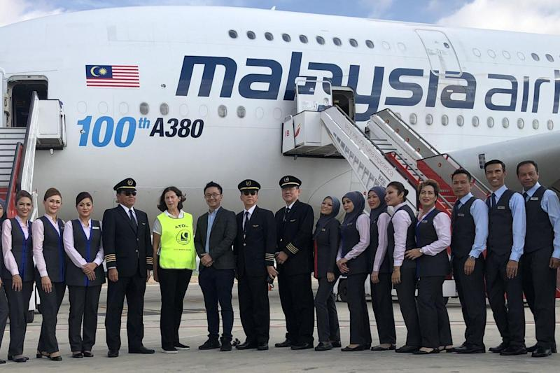 Rescue mission: Dame Deirdre Hutton (highly visible), chair of the Civil Aviation Authority, with the crew of a Malaysia Airlines jet at Palma airport: Simon Calder