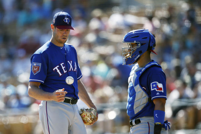 Texas Rangers starting pitcher Doug Fister, left, flips the ball in the air as he get a visit from catcher Robinson Chirinos, right, during the third inning of a spring training baseball game against the Chicago White Sox Tuesday, March 20, 2018, in Glendale, Ariz. (AP Photo/Ross D. Franklin)