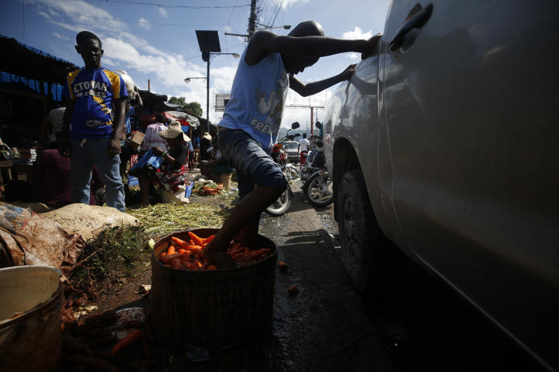 A youth cleans carrots by agitating them with his feet in a tub of murky water, at a market in Petionville, Port-au-Prince, Haiti, Wednesday, Oct. 2, 2019. There was a relative pause Wednesday in disturbances that have wracked Haiti's capital for weeks as protesters have tried to drive President Jovenel Moïse from power. (AP Photo/Rebecca Blackwell)