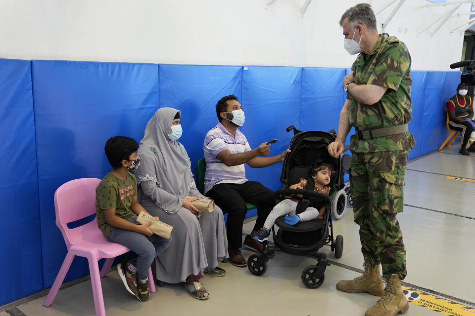 Rear Admiral Henrique Gouveia e Melo gives a Vaccination Task Force patch, like the one he wears on his shoulder, to a family at a vaccination center in Lisbon, Tuesday, Sept. 21, 2021. As Portugal nears its goal of fully vaccinating 85% of the population against COVID-19 in nine months, other countries want to know how it was able to accomplish the feat. A lot of the credit is going to Gouveia e Melo. (AP Photo/Armando Franca)