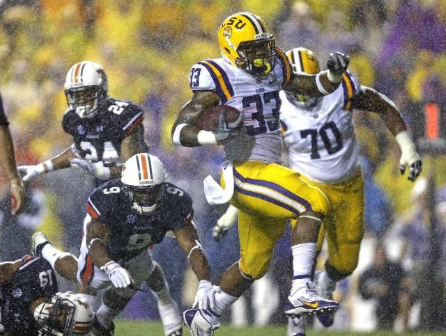 LSU running back Jeremy Hill (33) rushes past Auburn defensive backs Jermaine Whitehead (9), Ryan White (19) and Ryan Smith (24) on his second touchdown carry in the first half of an NCAA college football game in Baton Rouge, La., Saturday, Sept. 21, 2013. LSU offensive tackle La'el Collins (70) pursues. (AP Photo/Gerald Herbert)