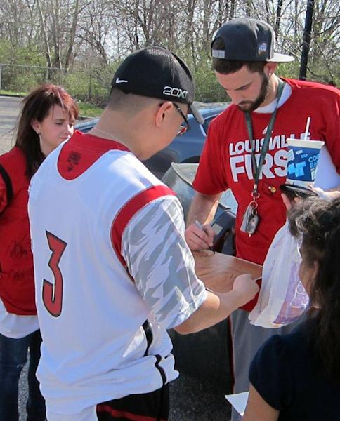 Louisville's Luke Hancock, the Final Four's Most Outstanding Player, signs an autograph for sophomore Ben Kao outside Billy Minardi Hall on Tuesday, April 9, 2013, in Louisville, Ky. The Cardinals beat Michigan 82-76 Monday night for the NCAA championship. (AP Photo/Gary Graves)