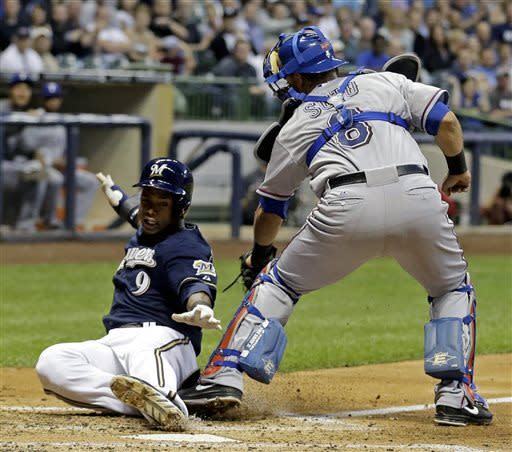 Texas Rangers catcher Geovany Soto (8) tags out Milwaukee Brewers' Jean Segura (9) at home during the third inning of a baseball game Wednesday, May 8, 2013, in Milwaukee. Segura tried to score from second on a hit by Aramis Ramirez. (AP Photo/Morry Gash)