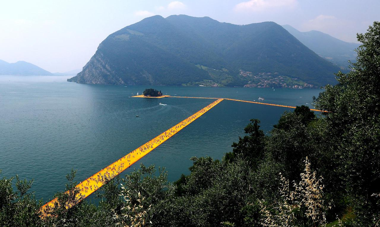 "<p>People walk on the installation ""The Floating Piers,"" by Bulgarian-born artist Christo on Lake Iseo, northern Italy, June 24, 2016. (Reuters/Stefano Rellandini) </p>"
