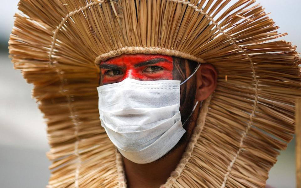 Also in Brasil, an indigenous man wears a protective mask during a protest against President Jair Bolsonaro's mining politics regarding indigenous lands, and demanding Brazilian Environment Minister Ricardo Salles' resignation, outside the Ministry of the Environment in Brasilia. - Getty