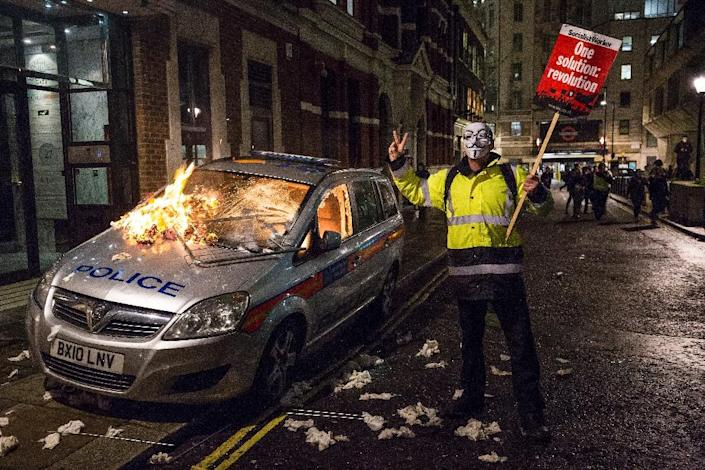 """An anti-capitalist protester wearing a Guy Fawkes mask holds a placard as he stands alongside a burning police car during the """"Million Masks March"""", organised by the group Anonymous, in London on November 5, 2015 (AFP Photo/Jack Taylor)"""