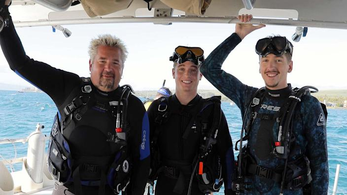 """Fieri and his sons pose on the Lahaina Divers boat en route to a reef in Lahaina, Hawaii, as seen in his new Discovery + series """"Guy: Hawaiian Style."""""""