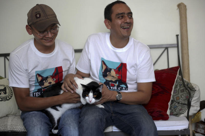 "CORRECTS DIEGO TO DAVID - David Cruz, left, and Sergio Chamorro pose with their cat Morris at their home in Xalapa, Mexico, Saturday, June 15, 2013. Put forth as candidate by Chamorro and a group of friends after they became disillusioned with the empty promises of politicians, Morris, a black-and-white cat with orange eyes, is running for mayor of Xalapa in eastern Mexico with the campaign slogan ""Tired of Voting for Rats? Vote for a Cat."" And he is attracting tens of thousands of politician-weary, two-legged supporters on social media. (AP Photo/Felix Marquez)"
