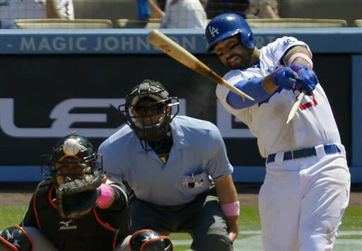 Los Angeles Dodgers' Matt Kemp, right, breaks his bat as he gets his 1,000th career hit as Miami Marlins catcher Miguel Olivo, left, and home plate umpire Chris Guccione look on during the fifth inning of a baseball game on Sunday, May 12, 2013, in Los Angeles. (AP Photo/Mark J. Terrill)