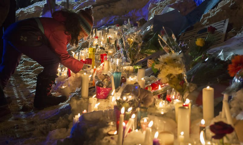 <p>A little girl places an object onto a row of tributes in Quebec City for those killed Sunday in an attack on a Quebec mosque. Photo from The Canadian Press </p>