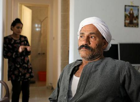 Nassif, an Egyptian Christian, who fled his home in Arish, sits with his family in a rented apartment on the edge of Suez Canal in Ismailia