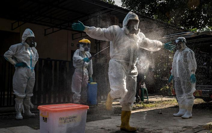 A volunteer undertaker is sprayed with disinfectant before recovering the body of a suspected Covid-19 victim in Yogyakarta, Indonesia on 22 July 2021 - Ulet Ifansasti/Getty Images