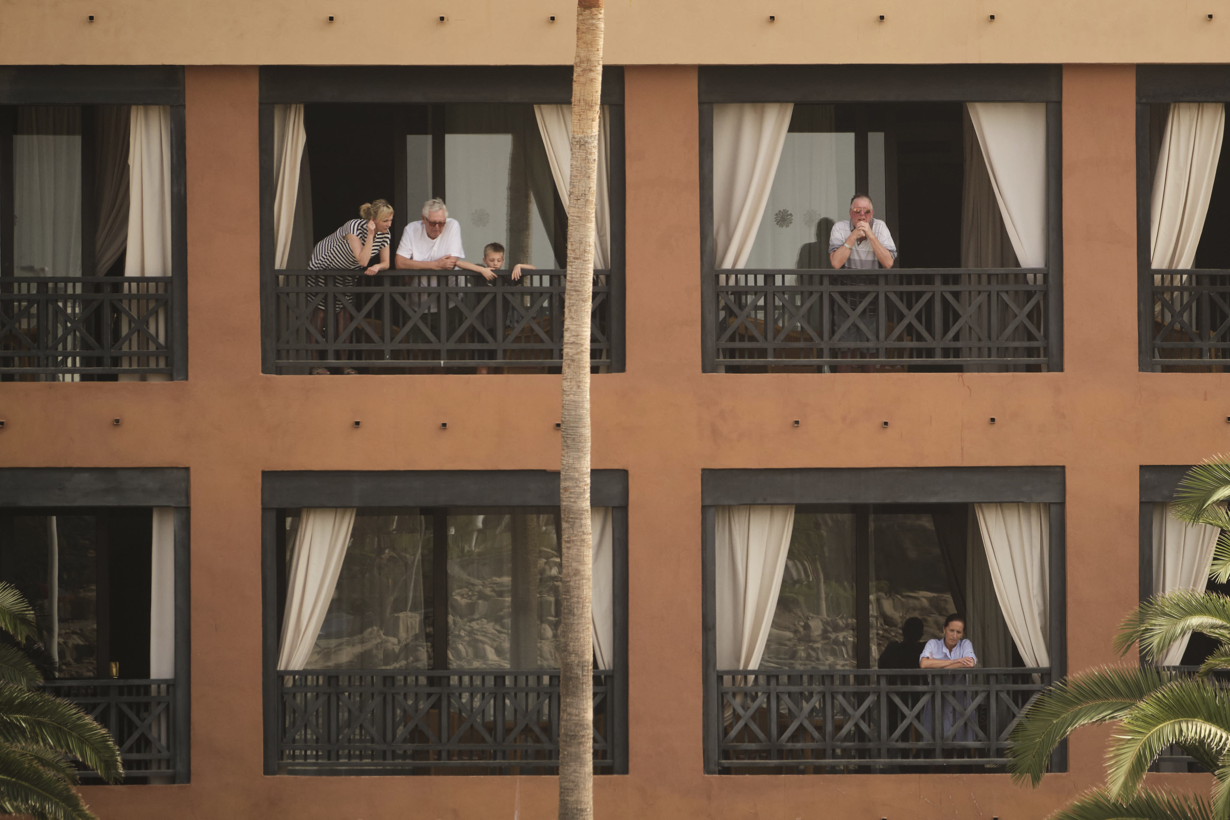 People stand on their balconies of the H10 Costa Adeje Palace hotel in the Canary Island of Tenerife, Spain, Tuesday, Feb. 25, 2020. Spanish officials say a tourist hotel on the Canary Island of Tenerife has been placed in quarantine after an Italian doctor staying there tested positive for the COVID-19 virus and Spanish news media says some 1,000 tourists staying at the complex are not allowed to leave. (AP Photo)