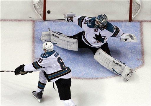 A puck shot by St. Louis Blues' David Backes, not shown, scores past San Jose Sharks goalie Antti Niemi, of Finland, and Justin Braun (61) during the second period in Game 2 of an NHL Stanley Cup first-round hockey playoff series Saturday, April 14, 2012, in St. Louis. (AP Photo/Jeff Roberson)