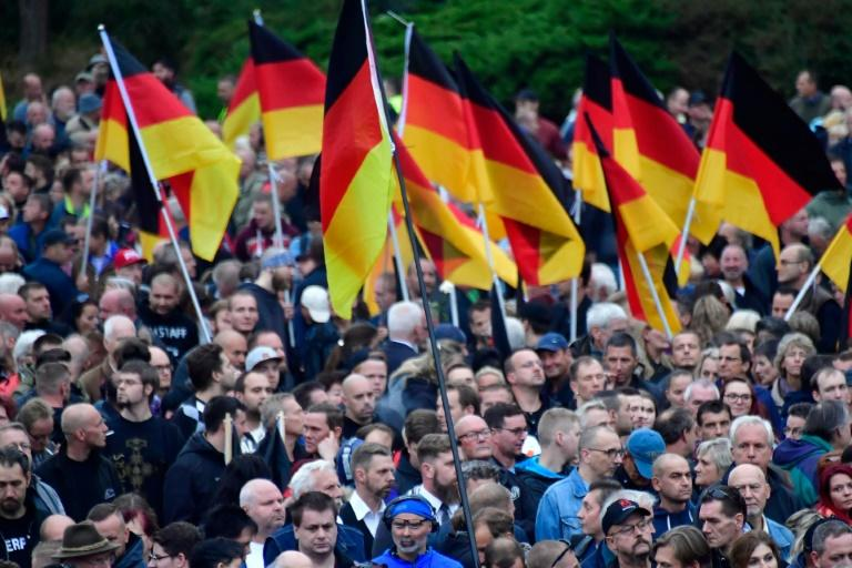 "Demonstrators brandish German flags at a rally organised by the right-wing populist ""Pro Chemnitz"" movement, the far-right Alternative for Germany (AfD) party and the anti-Islam Pegida movement in Chemnitz, scene of attacks by a racist mob in recent days"