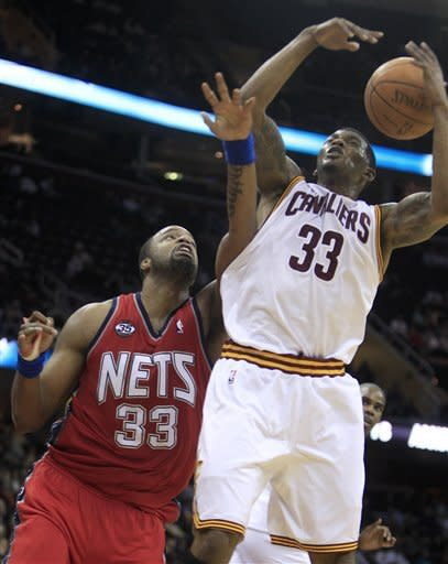 Cleveland Cavaliers' Alonzo Gee (33) grabs a rebound ahead of New Jersey Nets power forward Shelden Williams (33) in the fourth quarter in an NBA basketball game on Friday, Jan. 27, 2012, in Cleveland. The Nets won 99-96. (AP Photo/Tony Dejak)
