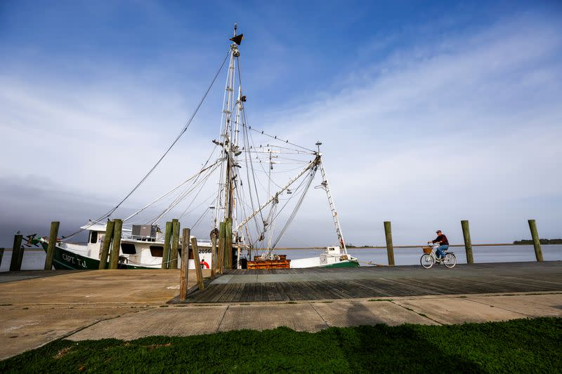 "A man bicycles past the shrimp boat ""Capt. T.J."" owned by the 13 Mile Seafood company while it is docked in Apalachicola, Florida"