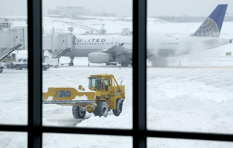 Machines clear snow off the tarmac at LaGuardia Airport in New York, Tuesday, Jan. 27, 2015. A storm packing blizzard conditions spun up the East Coast early Tuesday, pounding parts of coastal New Jersey northward through Maine with high winds and heavy snow. (AP Photo/Seth Wenig)