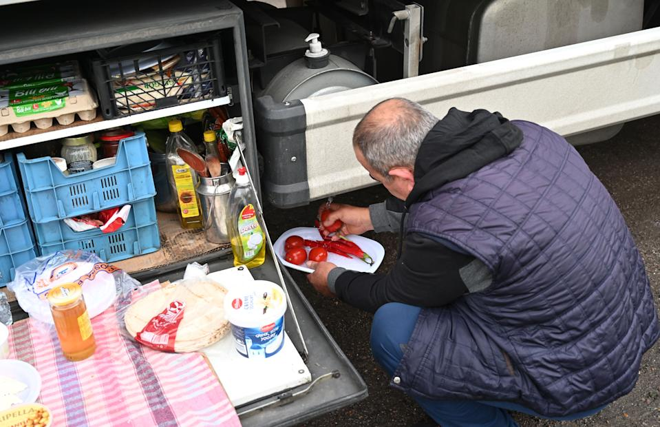 A Turkish long-haul truck driver prepares his breakfast at a truck stop off the M20 motorway which leads to the Port of Dover, near Ashford in Kent, south east England on December 22, 2020, as he queues unable to continue his journey after France closed its borders to accompanied freight arriving from the UK due to the rapid spread of a more-infectious new coronavirus strain. - Britain sought to sound a note of calm saying they were working as fast as possible to unblock trade across the Channel after France shut its borders to UK hauliers in a bid to contain a new variant of the coronavirus. (Photo by JUSTIN TALLIS / AFP) (Photo by JUSTIN TALLIS/AFP via Getty Images)