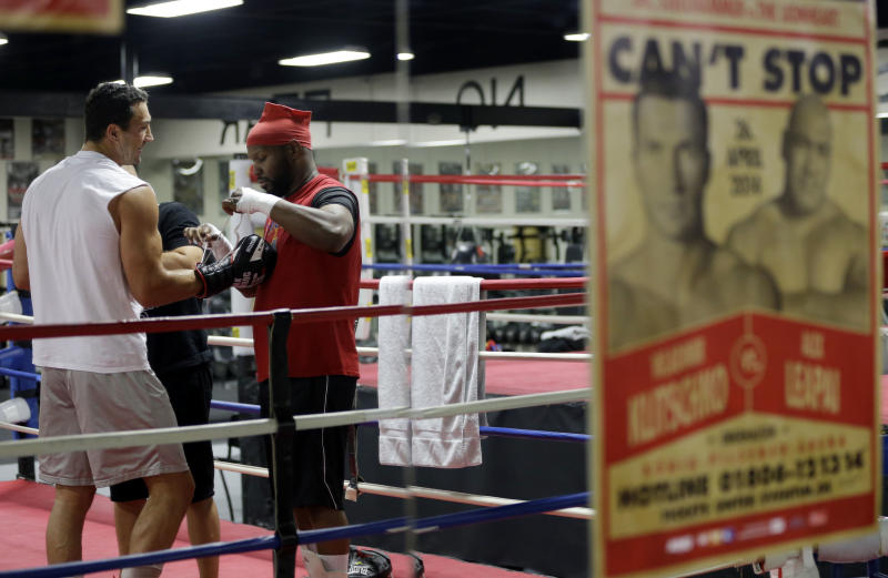 Undefeated heavyweight boxing champion Wladimir Klitschko, of Ukraine, left, has his gloves put on by sparring partner Jonathon Banks, right, while training at the Lucky Street Boxing Gym, Thursday, March 20, 2014, in Hollywood, Fla. Klitschko is preparing for his upcoming fight April 26 against Alex Leapai in Germany, advertised in the poster at right. (AP Photo/Lynne Sladky)
