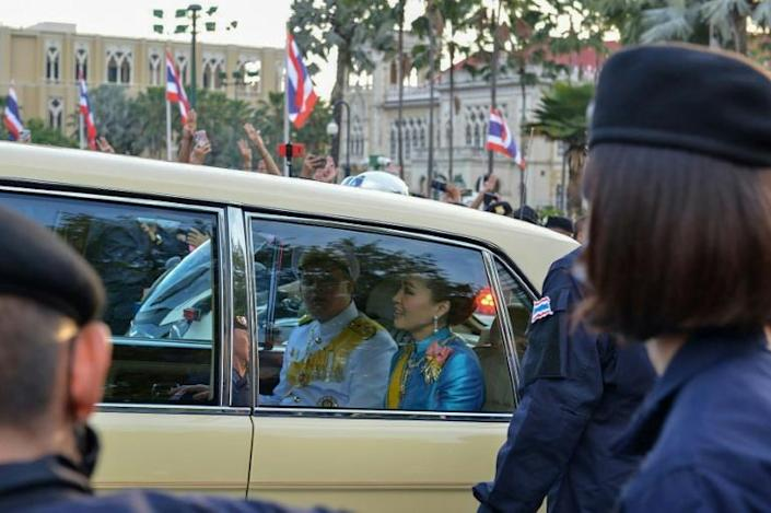 Thailand's Queen Suthida (C) and Prince Dipangkorn Rasmijoti (centre L) react inside a royal motorcade as it drives past a pro-democracy rally, as anti-government protesters (back) hold up their three-finger salute, in Bangkok on October 14, 2020