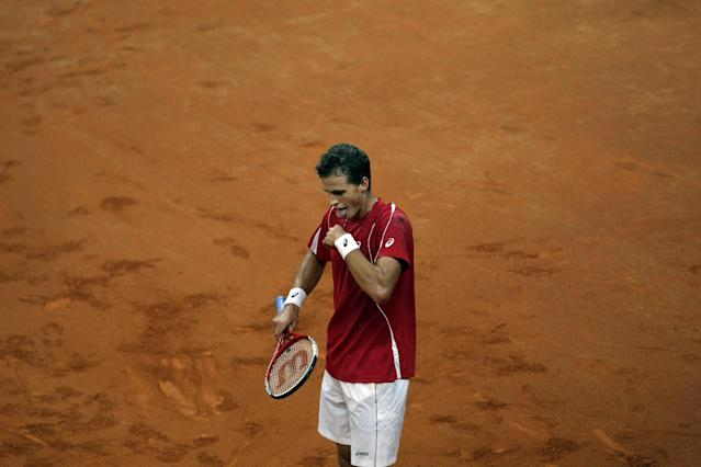 Canada's Vasek Pospisil sticks his tongue out after losing a point to Serbia's Novak Djokovic during their Davis Cup semifinals tennis match in Belgrade, Serbia, Friday, Sept. 13, 2013. (AP Photo/Marko Drobnjakovic)