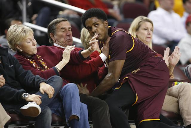 FILE - In this Jan. 9, 2014 file photo, Arizona State's Shaquielle McKissic runs into spectators sitting in courtside seats as he tries to prevent a ball from going out of bounds against Southern California during the second half of an NCAA college basketball game in Los Angeles. Oklahoma State All-American guard Marcus Smart is serving a three-game suspension for shoving a fan who later apologized for his actions. The incident shows how volatile the interaction between fans and athletes is becoming. (AP Photo/Danny Moloshok, File)