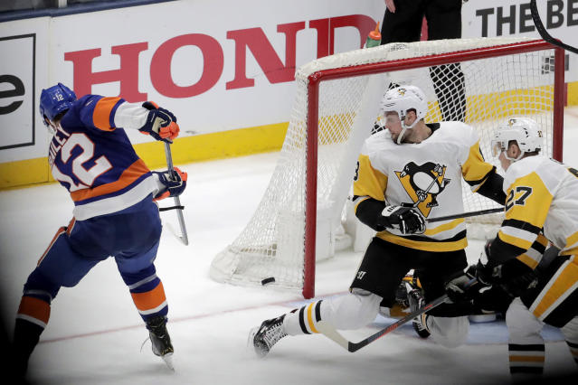 New York Islanders right wing Josh Bailey (12) scores during overtime of Game 1 of an NHL hockey first-round playoff series against the Pittsburgh Penguins, Wednesday, April 10, 2019, in Uniondale, N.Y. The Islanders won 4-3. (AP Photo/Julio Cortez)