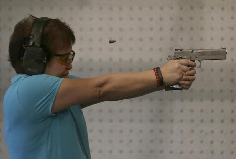 """In this Feb. 9, 2014 photo, Bureau of Internal Revenue Commissioner Kim Henares fires her pistol during target practice in a firing range at suburban Mandaluyong city, east of Manila, Philippines. The 53-year-old straight-talking chief has shifted her agency into """"law enforcement mode"""" with an aggressive anti-tax evasion campaign to catch cheats and raise collections. Henares is a lawyer and accountant whose hobbies include weekly trips to the firing range where she shoots off automatic pistols and assault rifles. Shooting has become one of her favorite pastimes since she was appointed in July 2010 by President Benigno Aquino III, a gun aficionado who introduced her to the sport. (AP Photo/Bullit Marquez)"""