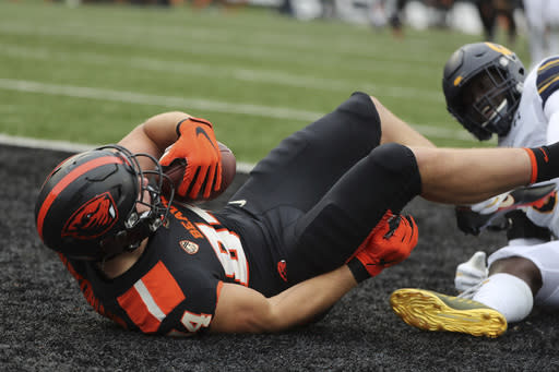 Oregon State tight end Teagan Quitoriano (84) is brought down in the end zone by California inside linebacker Kuony Deng (8) to score a touchdown on a pass from Oregon State quarterback Tristan Gebbia (3) during the first half of an NCAA college football game in Corvallis, Ore., Saturday, Nov. 21, 2020. (AP Photo/Amanda Loman)