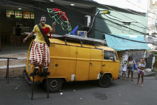 A street artist (L) holding an umbrella fixed with hearts makes a performance as he enters Rocinha slum in Rio de Janeiro March 13, 2014. The artist was giving out hearts to people who passed him, which he says is a symbol of peace. REUTERS/Pilar Olivares (BRAZIL - Tags: SOCIETY)
